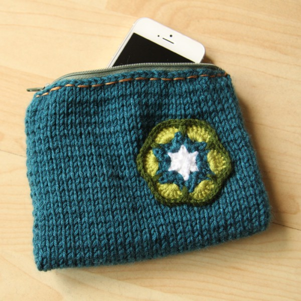 Knitted pouch with a crochet flower
